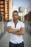Handsome muscular blond man standing in city environment Stock Photo