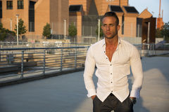 Handsome muscular blond man standing in city setting Stock Image