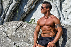 Handsome, muscular bodybuilder against white rocks Royalty Free Stock Images