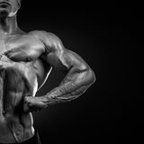 Handsome muscular bodybuilder posing on Front Lat Spread Stock Photos