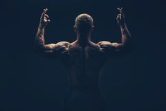 Handsome muscular bodybuilder posing over black Royalty Free Stock Images
