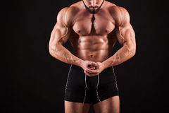 Handsome muscular bodybuilder posing over black background. Royalty Free Stock Photography