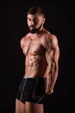Handsome muscular bodybuilder posing over black background. Handsome muscular bodybuilder posing over black background Royalty Free Stock Image