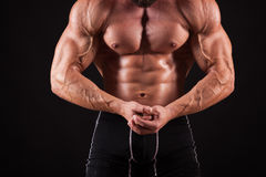 Handsome muscular bodybuilder posing over black background. Stock Image