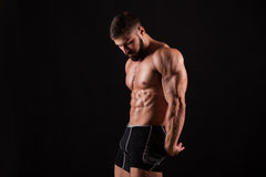 Handsome muscular bodybuilder posing over black background. Royalty Free Stock Photos