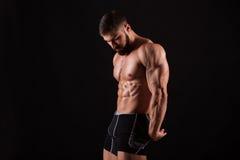 Handsome muscular bodybuilder posing over black background. Handsome muscular bodybuilder posing over black background Royalty Free Stock Photos