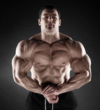 Handsome muscular bodybuilder posing over black background. Stock Photos