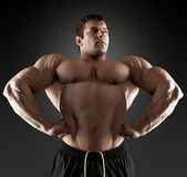 Handsome muscular bodybuilder posing over black background. royalty free stock photo