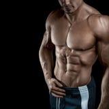 Handsome muscular bodybuilder posing over black background Stock Image