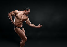 Handsome muscular bodybuilder posing over black background. Royalty Free Stock Images