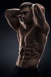 Handsome muscular bodybuilder posing over black background Royalty Free Stock Images