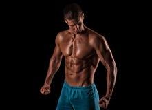 Handsome muscular bodybuilder posing over black background. Stock Photo