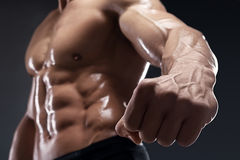 Handsome muscular bodybuilder shows his fist and vein. Royalty Free Stock Photos