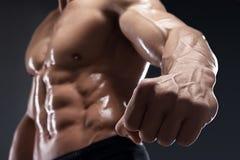 Handsome muscular bodybuilder shows his fist and vein. Handsome muscular bodybuilder shows his fist and vein, blood vessels. Studio shot on dark background royalty free stock photos