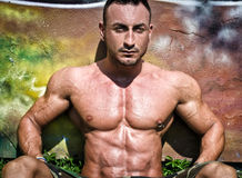 Handsome, muscular bodybuilder sitting against colorful wall Stock Images