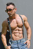 Handsome, muscular bodybuilder with suspenders shirtless Stock Photography