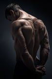 Handsome muscular bodybuilder turned back Stock Photos