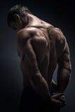 Handsome muscular bodybuilder turned back Stock Photos