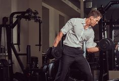 Handsome muscular businessman in formal clothes doing exercise with dumbbells in the gym. Royalty Free Stock Photography