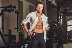 Handsome muscular businessman in an unbuttoned shirt doing exercise with a dumbbell in the gym. Royalty Free Stock Photography