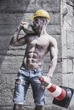 Handsome muscular construction worker standing. Shirtless in front of a concrete wall, looking away to a side Royalty Free Stock Image