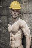 Handsome muscular construction worker standing. Shirtless in front of a concrete wall, looking at camera Stock Photo