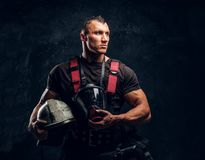 Handsome muscular fireman holding a helmet and oxygen mask standing in the studio against a dark textured wall. Portrait of a handsome muscular fireman holding a stock photos