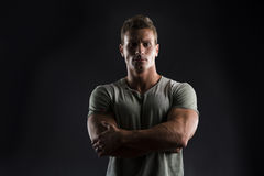 Handsome muscular fit young man on dark background with stern expression. Handsome muscular fit young man on dark background looking at camera, arms crossed on Royalty Free Stock Photo