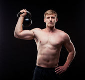 Handsome muscular guy with kettlebells isolated on Stock Images