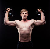 Handsome muscular guy with kettlebells isolated on Stock Photos