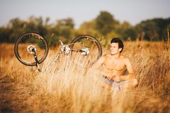 A handsome muscular guy with a naked torso sitting near a bicycle in the countryside in a field resting, listening to music and ho Royalty Free Stock Photos