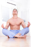 Handsome muscular half naked man doing yoga and meditating. Young handsome muscular half naked man doing yoga and meditating indoors in living room, domestic royalty free stock photography