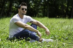 Handsome Muscular Hunk Man Outdoor in City Park. Or Countryside, Sitting on Grass. Showing Healthy Muscle Body While Looking away Royalty Free Stock Images