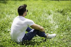 Handsome Muscular Hunk Man Outdoor in City Park. Or Countryside, Sitting on Grass. Showing Healthy Muscle Body While Looking away Royalty Free Stock Photo