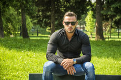 Handsome Muscular Hunk Man Outdoor in City Park. During Daytime, Wearing Black Shirt and Sunglasses Stock Images