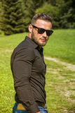 Handsome Muscular Hunk Man Outdoor in City Park. During Daytime, Wearing Black Shirt and Sunglasses Royalty Free Stock Photography