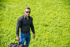 Handsome Muscular Hunk Man Outdoor in City Park. During Daytime, Wearing Black Shirt and Sunglasses Stock Photography