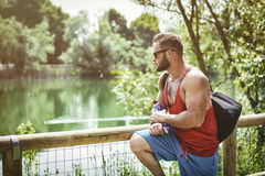 Handsome Muscular Hunk Man Outdoor in City Park. During Daytime, Wearing Tanktop and Sunglasses Stock Images