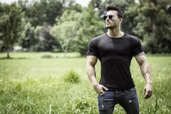 Handsome Muscular Hunk Man Outdoor in City Park. Or Countryside, Sitting on Grass. Showing Healthy Muscle Body While Looking away Stock Image
