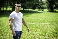 Handsome Muscular Hunk Man Outdoor in City Park. Or Countryside, Standing on Grass. Showing Healthy Muscle Body While Looking away Royalty Free Stock Photos