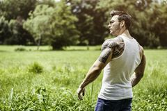Handsome Muscular Hunk Man Outdoor in City Park. Or Countryside, Standing on Grass. Showing Healthy Muscle Body While Looking away Royalty Free Stock Photography