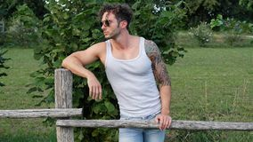 Muscular Hunk Man Outdoor in Countryside. Handsome Muscular Hunk Man Outdoor in Countryside Standing on Grass. Showing Healthy Muscle Body While Looking away Royalty Free Stock Images