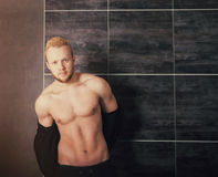 Handsome muscular male model near the wall Royalty Free Stock Photography