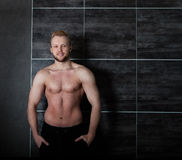 Handsome muscular male model near the wall Stock Photo