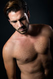 Handsome muscular male model posing over black background. Royalty Free Stock Photography