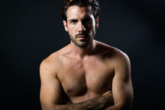 Handsome muscular male model posing over black background. Stock Photos