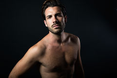 Handsome muscular male model posing over black background. Royalty Free Stock Images