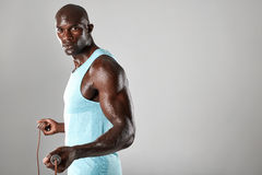 Handsome muscular male posing with jumping rope stock photo