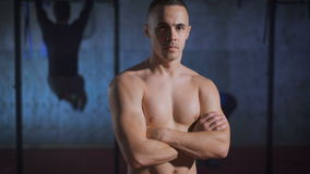 Handsome muscular man with arms crossed posing shirtless at the gym. stock footage