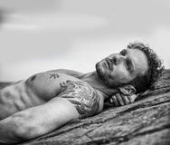 Handsome muscular man on the beach laying on rocks Stock Photography